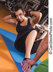 Sit up - Strong, fitness woman doing sit-ups in a gym as...