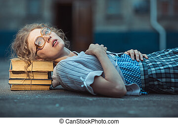 Funny crazy girl student with glasses lying on a pile of...