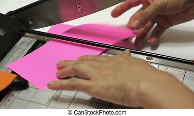 Craft Paper Cutting on Guillotine - Woman cuts pink craft...