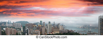 Sunset sky over Hong Kong bay. Aerial view of city skyscrapers
