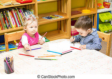 Two little kids drawing with colorful pencils in preschool...