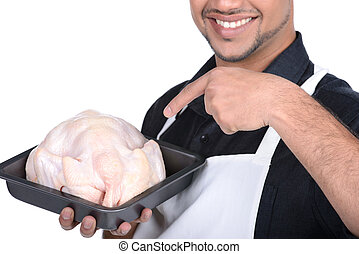 Butcher - Young handsome man holding chicken professional...