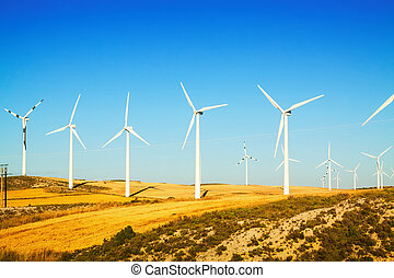 Wind farm at farmland in summer Aragon, Spain
