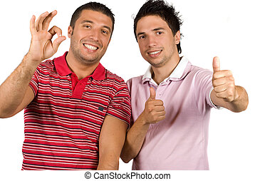 Friends giving okay sign and thumb up - Portrait of two...