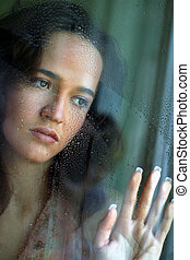 The girl behind glass - Sad woman behind a wet window