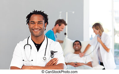 Smiling African doctor with his colleagues in the background
