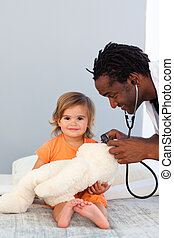 Pediatrician exams a little girl with stethoscope in a...