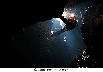 Spelunker rappelling in a sinkhole - Spelunker rappelling on...