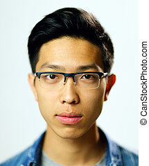 Closeup portrait of a young serious asian man on gray...