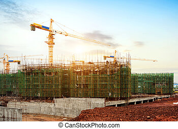 Housing construction site - Cranes on a sunset background