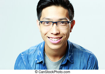 Portrait of a young smiling man in glasses on gray background