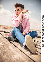 relaxed young fashion man sitting outdoor