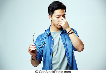 Asian man holding glasses and rubbing his eyes on gray...