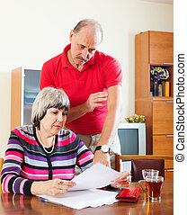 couple calculating family budget - serious mature couple...