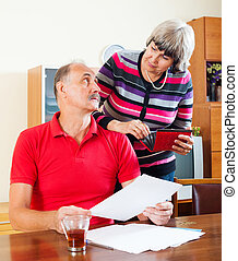 Mature couple calculating family budget at home