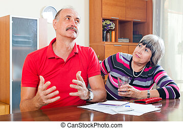 Mature man and woman having financial problems at home