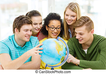 five smiling student looking at globe at school - education,...