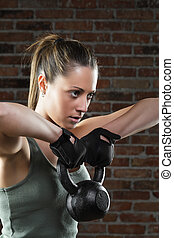 Young fit woman lifting kettle bell on brick background -...