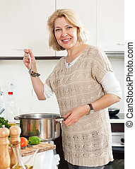 Smiling housewife with ladle cooking soup in pan at kitchen...
