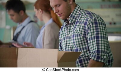 Busy Packer - Tilt of man in casual checked shirt busy...