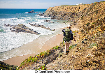 female hiker with rucksack - hiker on hiking trail coast...