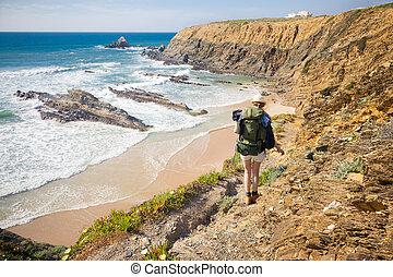 female hiker with rucksack - hiker on hiking trail coast...