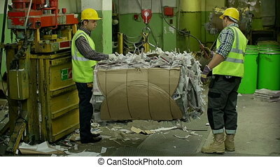 Recycling Industry - Two male laborers in helmets loading...