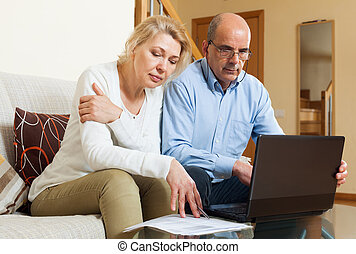 Family reading finance documents together and using laptop...