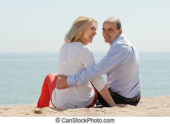 Rear view of loving mature couple at beach