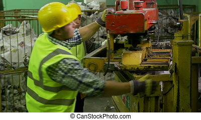 Recycling Plant Routine - Two coworkers operating press...