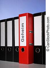 Red folder between a series of black ring binders.