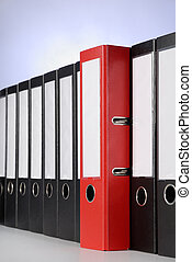 Red ring binder - A red ring binder between a series of...