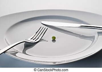 Plate with cutlery and a pea - Plate with knife, fork and a...