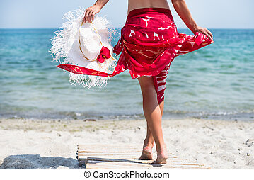 Woman walks at the beach - Beautiful woman with white hat...
