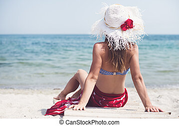 Woman sitting at the beach - Beautiful woman iwith hat...