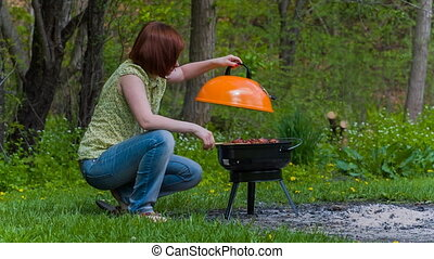 Woman grilling in the park - Young woman grilling liver in...