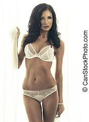 Beautiful young brunette woman posing, wearing white bra. Studio shot.