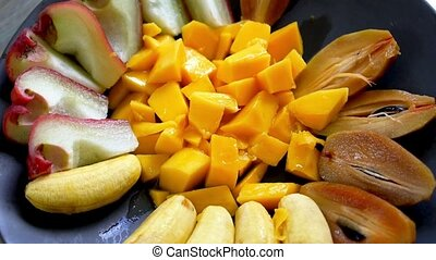 Eating healthy fresh exotic fruits from the plate Tasty...