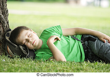 Dreams under tree - Boy in green shirt sleeping in park...