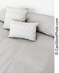 Grey bed linen and pillows - Bed with grey bed linen and...