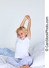 Blonde girl stretching in bed after sleeping