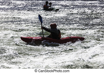 kayaker - silhouette of active male kayaker in rough water