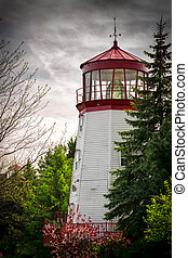 Old Lighthouse Nestled Among Trees - An old white and red,...