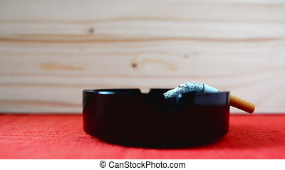Cigarette burning in black ashtray on the table, ash...