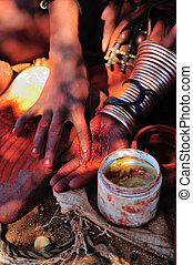 Himba woman mixing red ochre with petroleum jelly to apply...