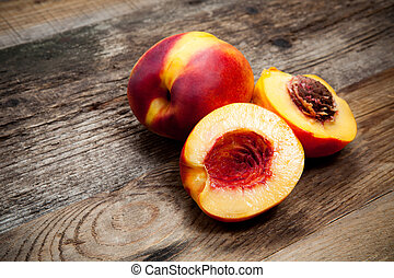 Fresh nectarines on wooden table