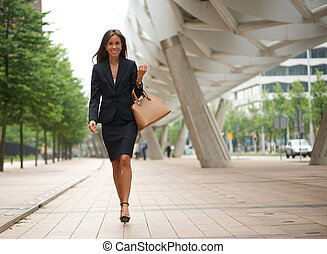 Business woman walking in the city with handbag - Portrait...