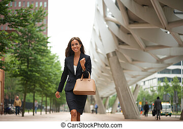 Business woman with handbag walking - Portrait of a business...