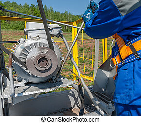 repair oil equipment - Worker repairing motor of the...