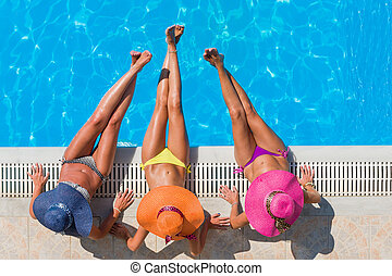 Girls relaxing in a swimming pool - Top view of a three...